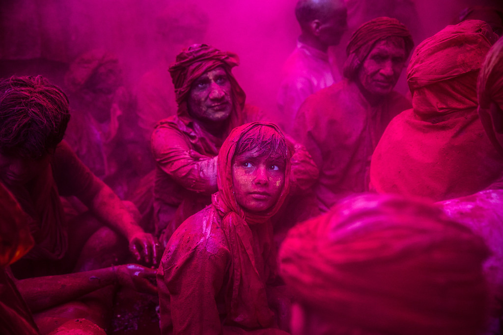 . A boy looks on as Hindu devotees play with color during Lathmaar Holi celebrations on March 21, 2013 in the village of Barsana, near Mathura, India. The tradition of playing with colours on Holi draws its roots from a legend of Radha and the Hindu God Krishna. It is believed that young Krishna was jealous of Radha\'s fair complexion since he himself was himself very dark. After questioning his mother Yashoda on the darkness of his complexion, Yashoda, teasingly asked him to colour Radha\'s face in which ever colour he wanted. In a mischievous mood, Krishna applied colour on Radha\'s face. The tradition of applying color on one\'s beloved is being religiously followed till date. (Photo by Daniel Berehulak/Getty Images)