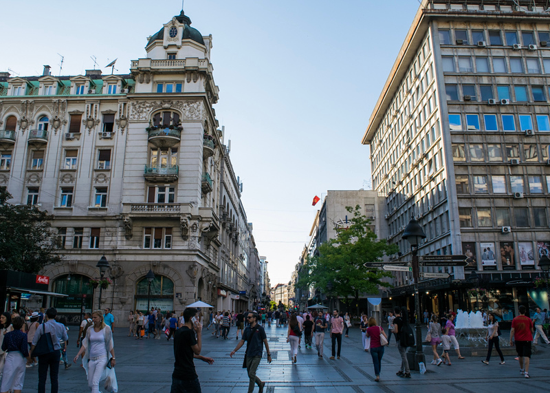 city scene with people walking on the street with classical buidings in the background