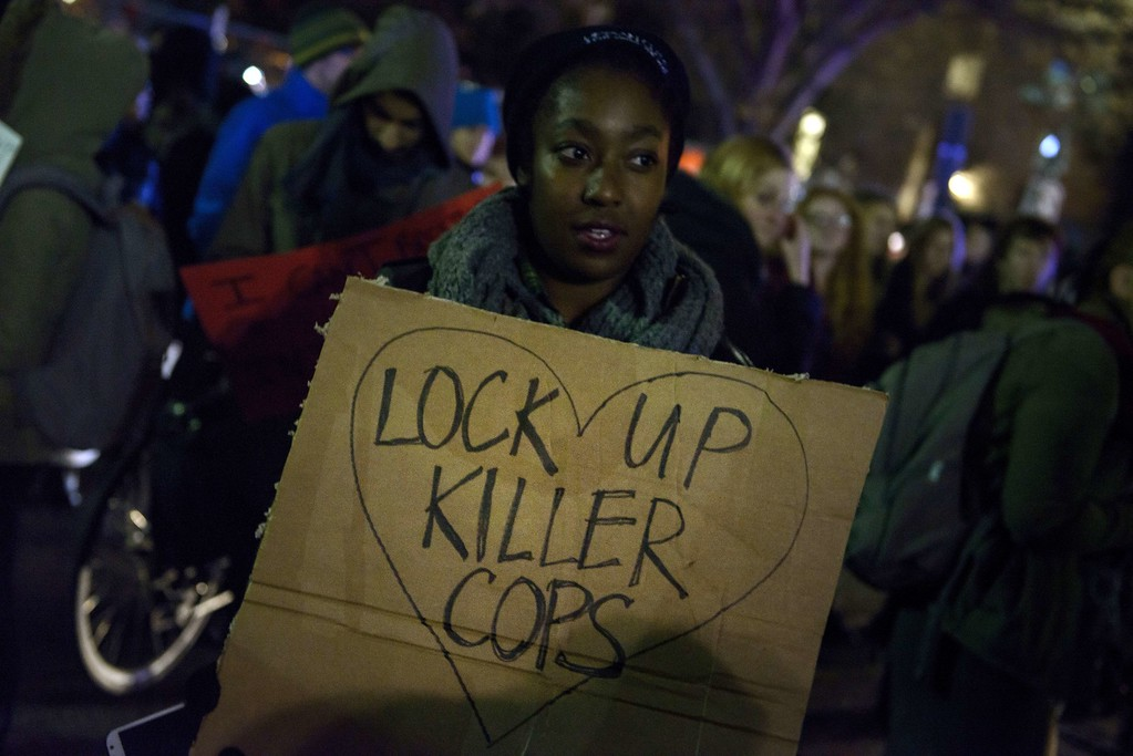 . An activist holds up a sign during a protest December 4, 2014 in Washington, DC,  against the police deaths of Michael Brown in Ferguson, Missouri  and Eric Garner in Staten Island, New York.  AFP PHOTO/Brendan SMIALOWSKI/AFP/Getty Images