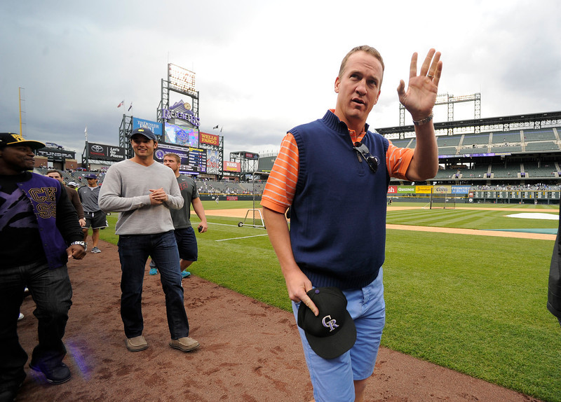 . Denver Broncos Peyton Manning waves to the crown as he walks down the warning track with some of the offensive line and a few defensive players to watch the Colorado Rockies New York Yankees batting practice May 7, 2013 at Coors Field. (Photo By John Leyba/The Denver Post)