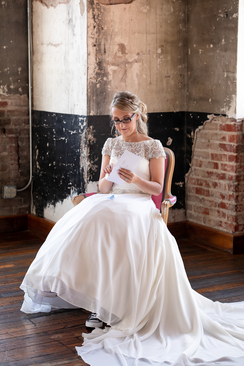 bride sitting in a red chair openin a letter with exposed brick walls behind her