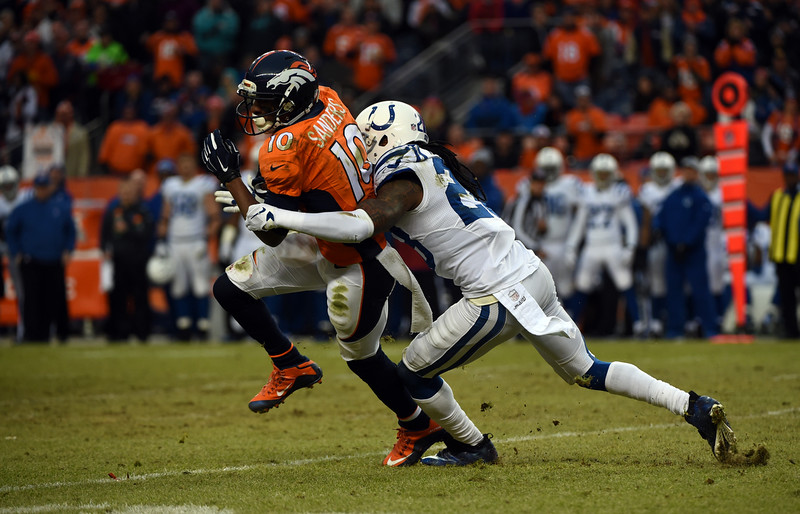 . Emmanuel Sanders (10) of the Denver Broncos makes a catch and is hit by Greg Toler (28) of the Indianapolis Colts during the second quarter.  The Denver Broncos played the Indianapolis Colts in an AFC divisional playoff game at Sports Authority Field at Mile High in Denver on January 11, 2015. (Photo by Tim Rasmussen/The Denver Post)