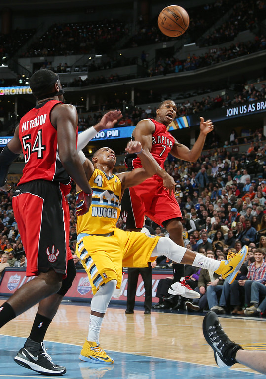 . Toronto Raptors guard Kyle Lowry, right, deflects a shot by Denver Nuggets guard Randy Foye, center, as Raptors forward Patrick Patterson looks on in the third quarter of  an NBA basketball game in Denver, Friday, Jan. 31, 2014. (AP Photo/David Zalubowski)