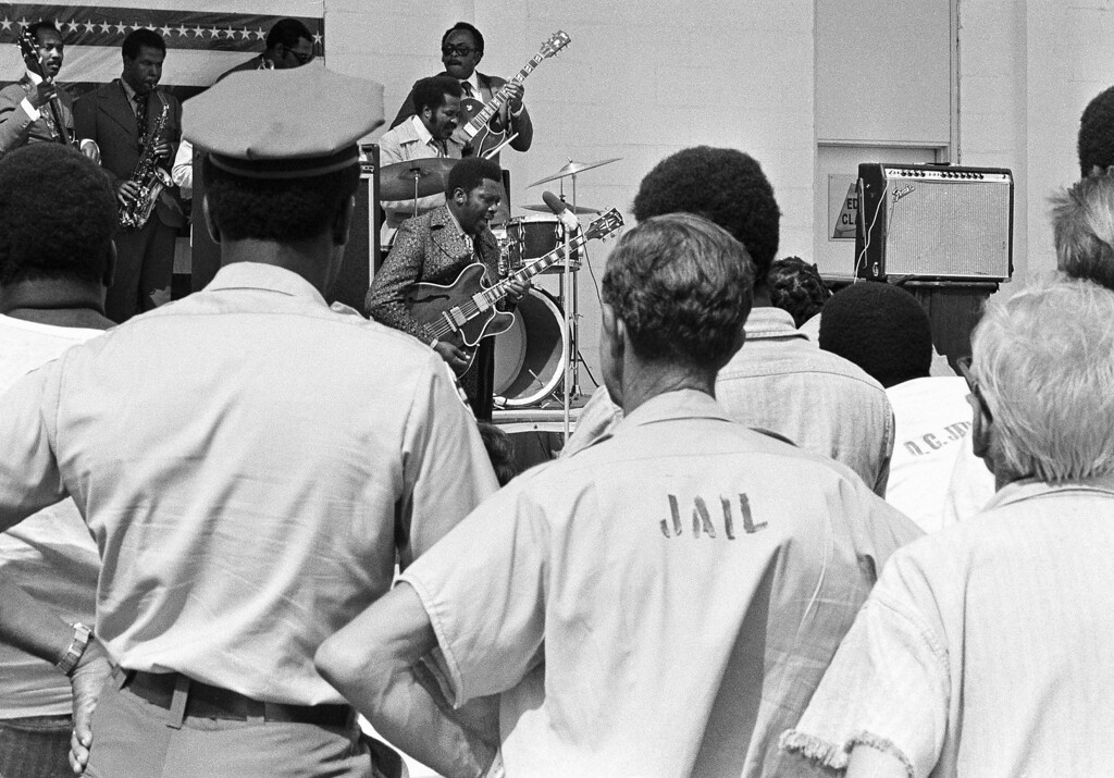 . A group of prisoners at the Dade County stockade listen to B.B. King entertained them outside their cells, Sept. 23, 1971 in Miami, Fla.  (AP Photo)