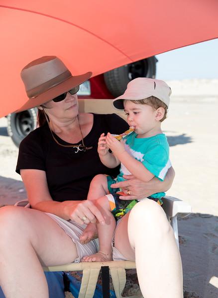 Caleb eating a snack with mam on the beach.jpg