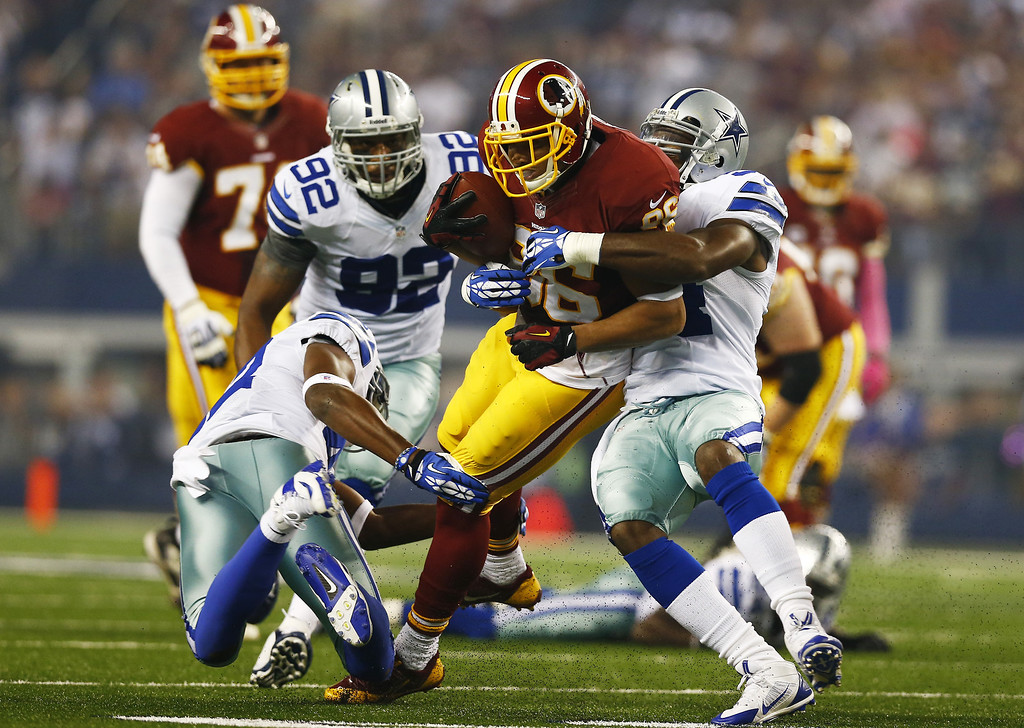 . Jordan Reed #86 of the Washington Redskins is tackeled by Barry Church #42, Jason Witten #82 and Kyle Wilber #51 during the first quarter on October 13, 2013 in Arlington, Texas.  (Photo by Tom Pennington/Getty Images)