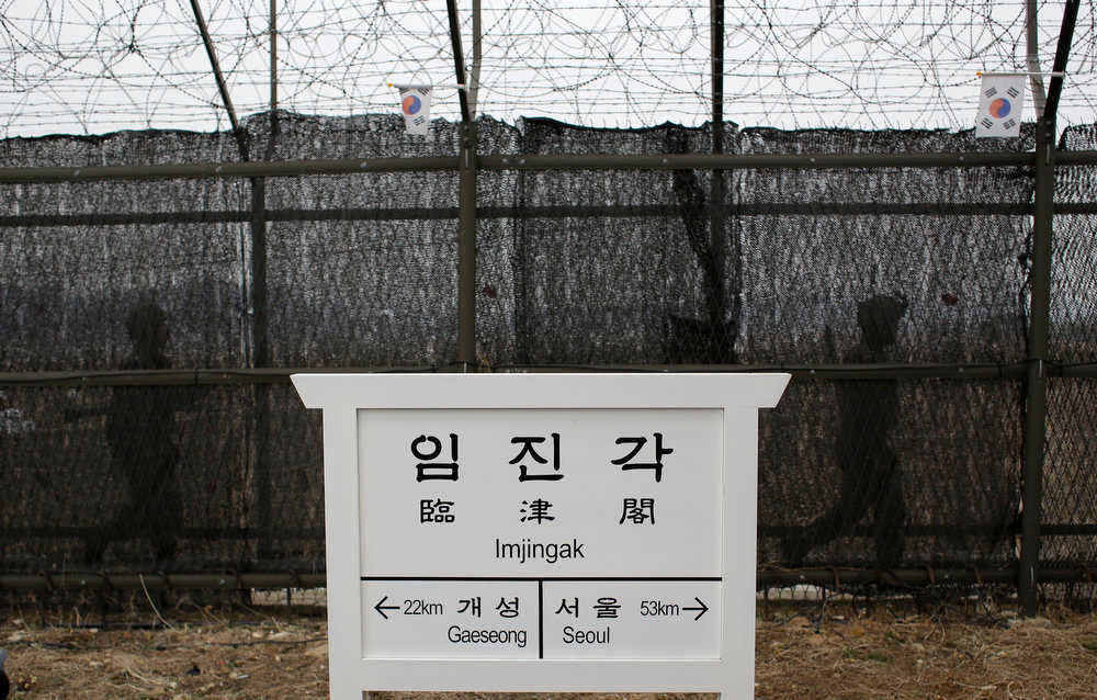 ". South Korean army soldiers patrol along a barbed-wire fence near a directional sign showing the distance to North Korea\'s Kaesong city  and South Korea\'s capital Seoul at the Imjingak Pavilion near the border village of the Panmunjom, which separated the two Koreas since the Korean War, in Paju, north of Seoul, South Korea, Friday, April 5, 2013. After a series of escalating threats, North Korea has moved a missile with ""considerable range\"" to its east coast, South Korea\'s defense minister said Thursday. But he emphasized that the missile was not capable of reaching the United States and that there are no signs that the North is preparing for a full-scale conflict. (AP Photo/Lee Jin-man)"
