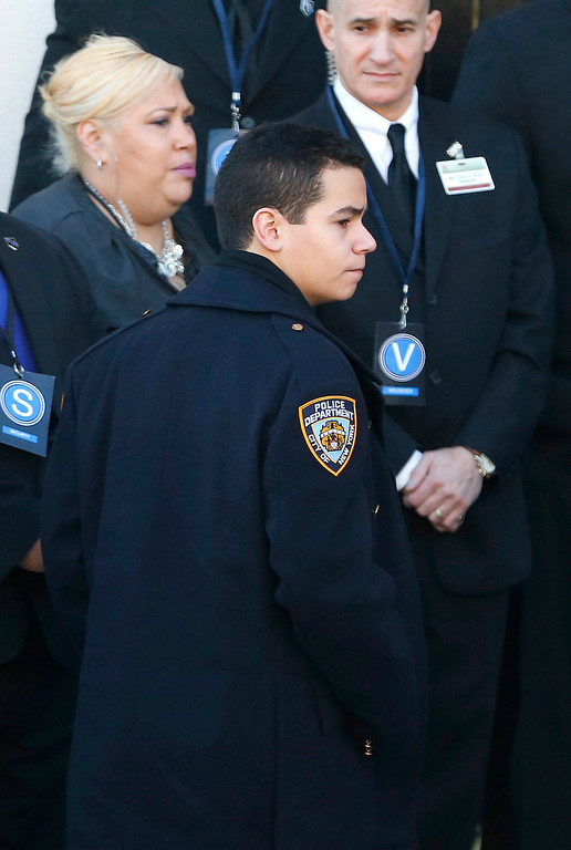 . Justin Ramos, son of New York City police officer Rafael Ramos, arrives at Christ Tabernacle Church, in the Glendale section of Queens, wearing a police jacket before funeral services for his father, Saturday, Dec. 27, 2014, in New York. Ramos and his partner, officer Wenjian Liu, were killed Dec. 20 as they sat in their patrol car on a Brooklyn street. The shooter, Ismaaiyl Brinsley, later killed himself. (AP Photo/Julio Cortez)