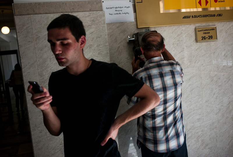 August 2011, Tbilisi, Georgia:  Men with the latest mobile phone and old phone in the lobby of Georgian Parliament.  Since 2006 the BTC has allowed Azerbaijan to export its oil to world markets through Georgia and Turkey, thus avoiding Russia.  It has given Azerbaijan a greater sense of independence and a new role for Georgia in Europe's energy security to the annoyance of Russia.  Some blame the BTC for Russia's continued covert involvement in regional latent conflicts especially the South Ossetian crisis which led to the Russia-Georgia war.