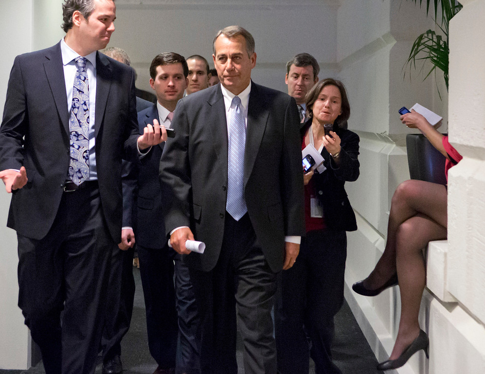 """. Reporters pursue Speaker of the House John Boehner, R-Ohio, as he walks to a closed-door meeting with GOP members of the House as Congress in Washington, Monday, Dec. 31, 2012, as Senate and House leaders rush to assemble a last-ditch agreement to head off the automatic tax hikes and spending cuts set to take effect Jan. 1, 2013. The House will miss the midnight Monday deadline lawmakers set for voting to avoid the \""""fiscal cliff.\""""  (AP Photo/J. Scott Applewhite)"""