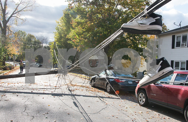 10/30/17 Wesley Bunnell | Staff At approximately 8:30pm on Sunday night a falling tree took down a utility pole and its electric lines causing a transformer to explode startling residents on Summer St. Sneakers hang from electrical wires near street level caused by a down utility pole.