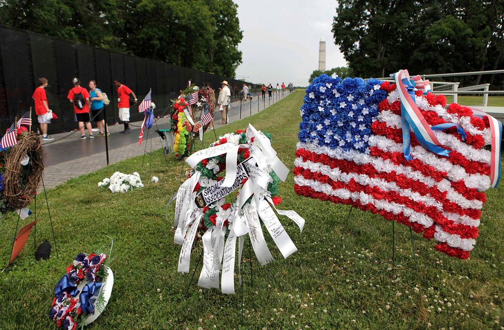 . The U.S. national flag composed of flowers is placed near the Vietnam Veterans Memorial wall etched with names of more than 58,000 U.S. servicemen and women who died in the war, in Washington May 23, 2013. Memorial Day will fall on May 27 this year.    REUTERS/Yuri Gripas