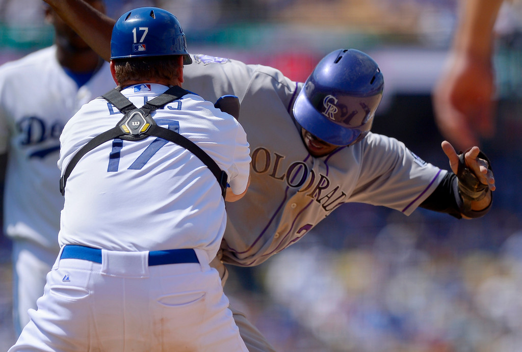 . Colorado Rockies\' Dexter Fowler, right, is tagged out by Los Angeles Dodgers catcher A.J. Ellis after being caught in a rundown between first and second during the sixth inning of their baseball game on Sunday, July 14, 2013, in Los Angeles. (AP Photo/Mark J. Terrill)