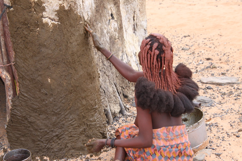 Himba woman spreading dung on house