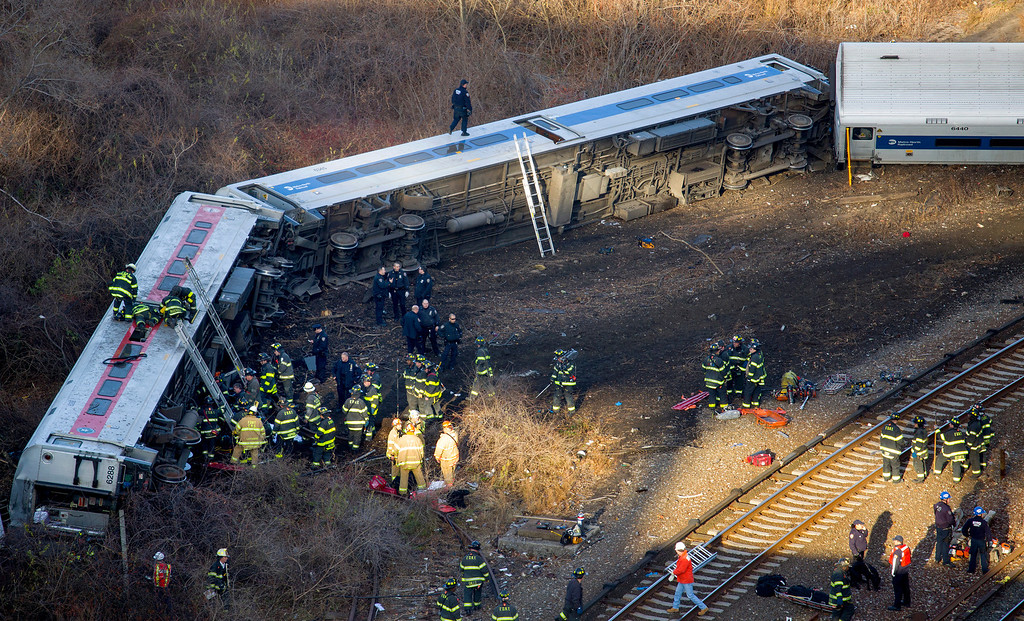 . First responders work the scene of a derailment of a Metro-North passenger train in the Bronx borough of New York Sunday, Dec. 1, 2013. The train derailed on a curved section of track in the Bronx on Sunday morning, coming to rest just inches from the water and causing multiple fatalities and dozens of injuries, authorities said. Metropolitan Transportation Authority police say the train derailed near the Spuyten Duyvil station. (AP Photo/Craig Ruttle)