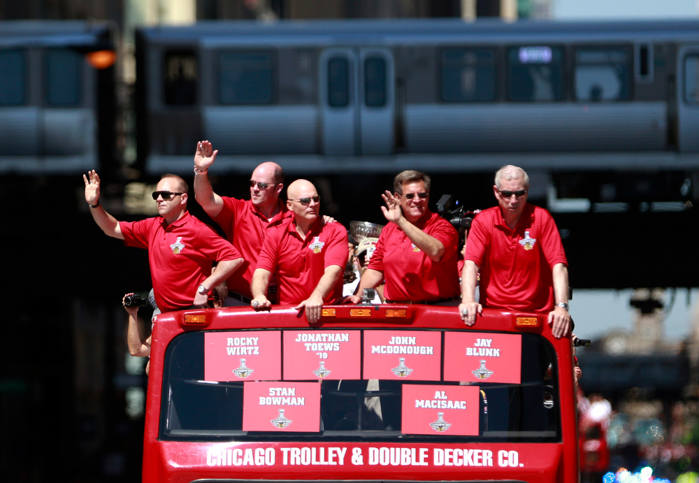 . The Chicago Blackhawks\' executive staff, from left, General Manager Stan Bowman, Vice presidents Al Macisaac, Jay Blunk, owner Rocky Wirtz, and President Jim McDonough, ride in the 2013 Stanley Cup Champion victory parade down Washington Street Friday, June 28, 2013 in Chicago. The Blackhawks celebrate the team\'s second championship in four years. (AP Photo/Scott Eisen)