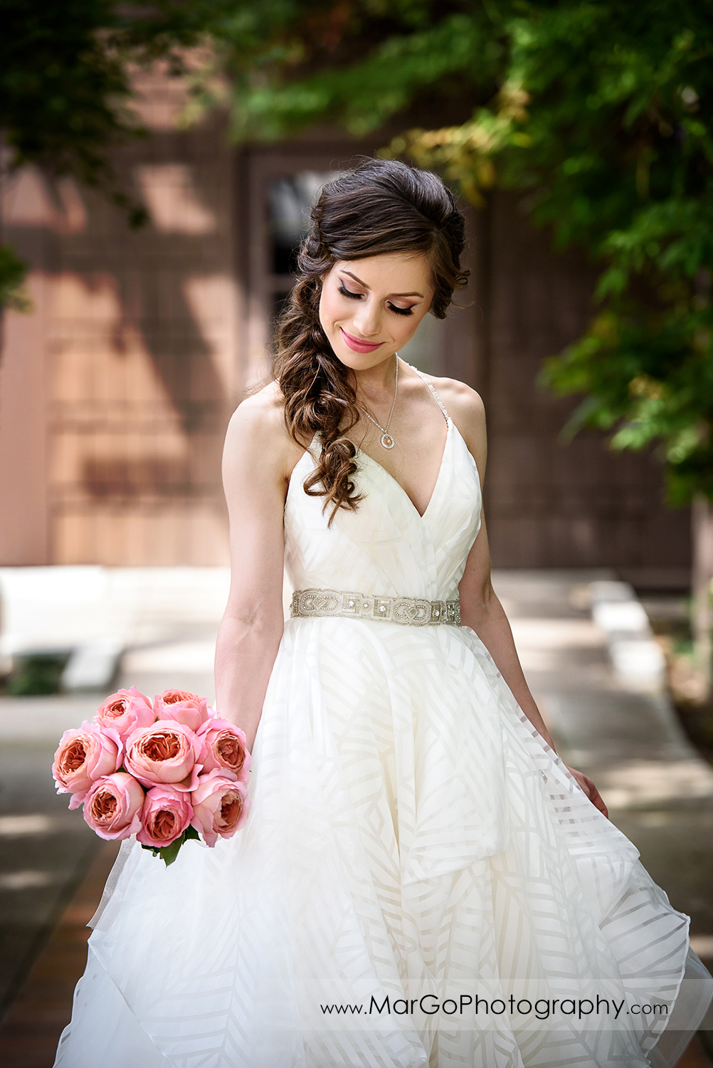 3/4 poze portrait of bride looking at pink flower bouquet at Saratoga Foothill Club