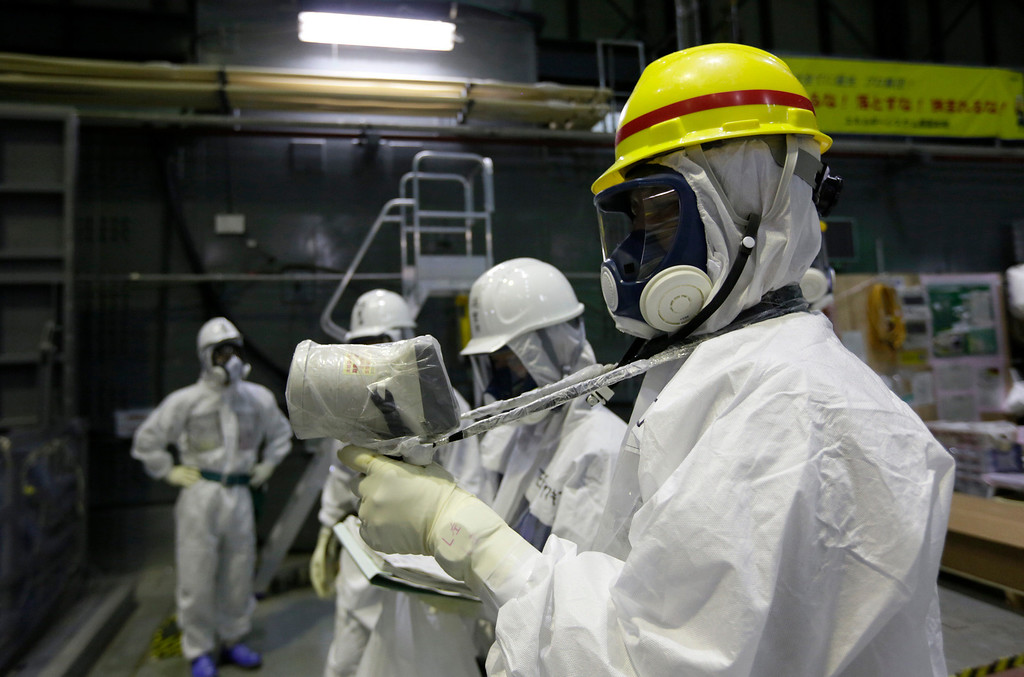 . An official of the Tokyo Electric Power Co., wearing a protective suit and a mask, measures radiation inside the building housing the Unit 4 reactor at the Fukushima Dai-ichi nuclear power plant in Okuma, Fukushima Prefecture, Japan, Thursday, Nov. 7, 2013. (AP Photo/Kimimasa Mayama, Pool)