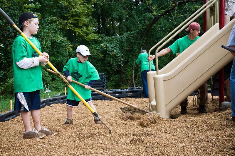 Carter (age 9) and Cameron (age 6) Brackman help to spread out the mulch around a playground.