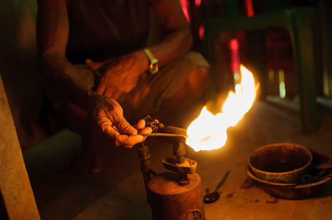 . Mine owner Gil Mercado, 70, heats a lump of gold using a blowtorch on April 23, 2014 in Pinut-An, Philippines. All excess water must be evaporated so the gold can be accurately weighed, on April 23, 2014 in Pinut-An, Philippines. (Photo by Luc Forsyth/Getty Images)