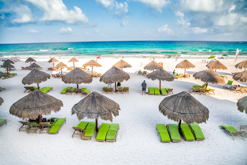 White sand beach and palapas in Cancun, Mexico