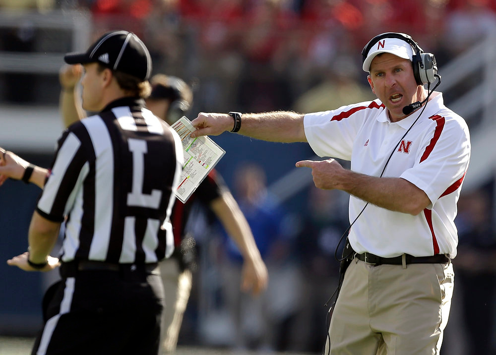 Description of . Nebraska head coach Bo Pelini, right, shouts at line judge Walt Colman, left, during the first half of the Capital One Bowl NCAA football game against Georgia, Tuesday, Jan. 1, 2013, in Orlando, Fla. (AP Photo/John Raoux)