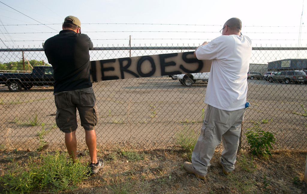 . Two men place a hero sign in front of Prescott Fire Station #7 on Monday, July 1, 2013, in Prescott, Ariz.  Eighteen firefighters from the Prescott Fire Department\'s Granite Mountain Hotshots team and a 19th firefighter from another crew were killed battling the Yarnell Hill Fire on Sunday. The Granite Mountain Hotshots were based out of Prescott Fire Station #7. David Wallace/The Arizona Republic  (AP Photo/The Arizona Republic, Dasvid Wallace)