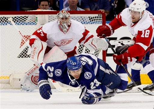 . Tampa Bay Lightning right wing J.T. Brown (23) goes down as he gets  with Detroit Red Wings center Joakim Andersson (18) in front of the net guarded by Red Wings goalie Petr Mrazek (34) during the second period in Game 1 of an NHL hockey first-round playoff series, Thursday, April 16, 2015, in Tampa, Fla. (Dirk Shadd/Tampa Bay Times via AP)