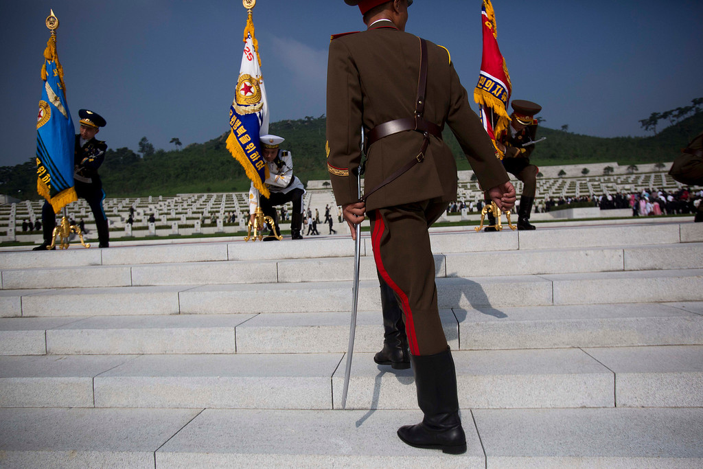 . North Korean honor guard soldiers lift their flags at an opening ceremony for a cemetery for Korean War veterans on Thursday, July 25, 2013 in Pyongyang, North Korea marking the 60th anniversary of the signing of the armistice that ended hostilities on the Korean peninsula. (AP Photo/David Guttenfelder)