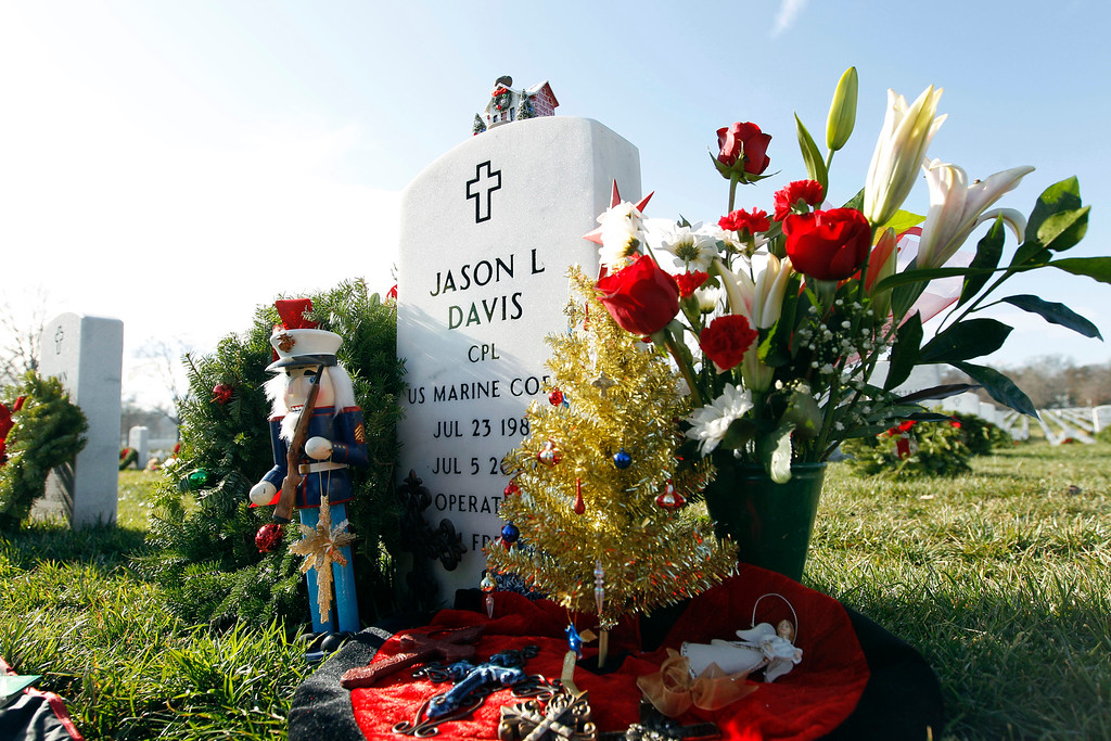 . The headstone of Marine Cpl. Jason L. Davis is decorated by his mother Diane Travis as a wreath is placed at each grave at Arlington National Cemetery in Arlington, Va. on Saturday, Dec. 15, 2012, during Wreaths Across America Day. Wreaths Across America was started in 1992 at Arlington National Cemetery by Maine businessman Morrill Worcester and has expanded to hundreds of veterans\' cemeteries and other locations in all 50 states and beyond. (AP Photo/Jose Luis Magana)