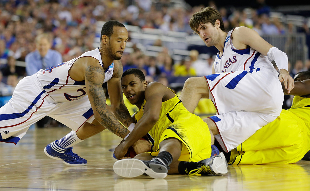 . Michigan\'s Glenn Robinson III ,battles for a loose ball with Kansas\' Travis Releford, and Jeff Withey, right, during the second half of a regional semifinal game in the NCAA college basketball tournament, Friday, March 29, 2013, in Arlington, Texas. (AP Photo/Tony Gutierrez)