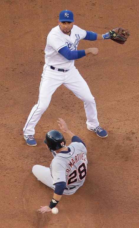 . Kansas City Royals second baseman Omar Infante throws to first for the double play hit into by Detroit Tigers\' Torii Hunter after getting J.D. Martinez (28) out at second during the third inning of a baseball game Thursday, July 10, 2014, in Kansas City, Mo. (AP Photo/Charlie Riedel)