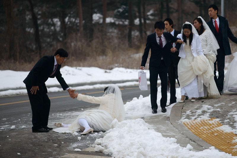 ". A groom helps his bride after she slipped on the ice as they arrive for a mass wedding event held by the Unification Church in Gapyeong on February 12, 2014. Unification Church members forming 2500 couples from 52 countries were married in a mass wedding in South Korea -- only the second such event since the death of their ""messiah\"" and controversial church founder Sun Myung Moon. (ED JONES/AFP/Getty Images)"