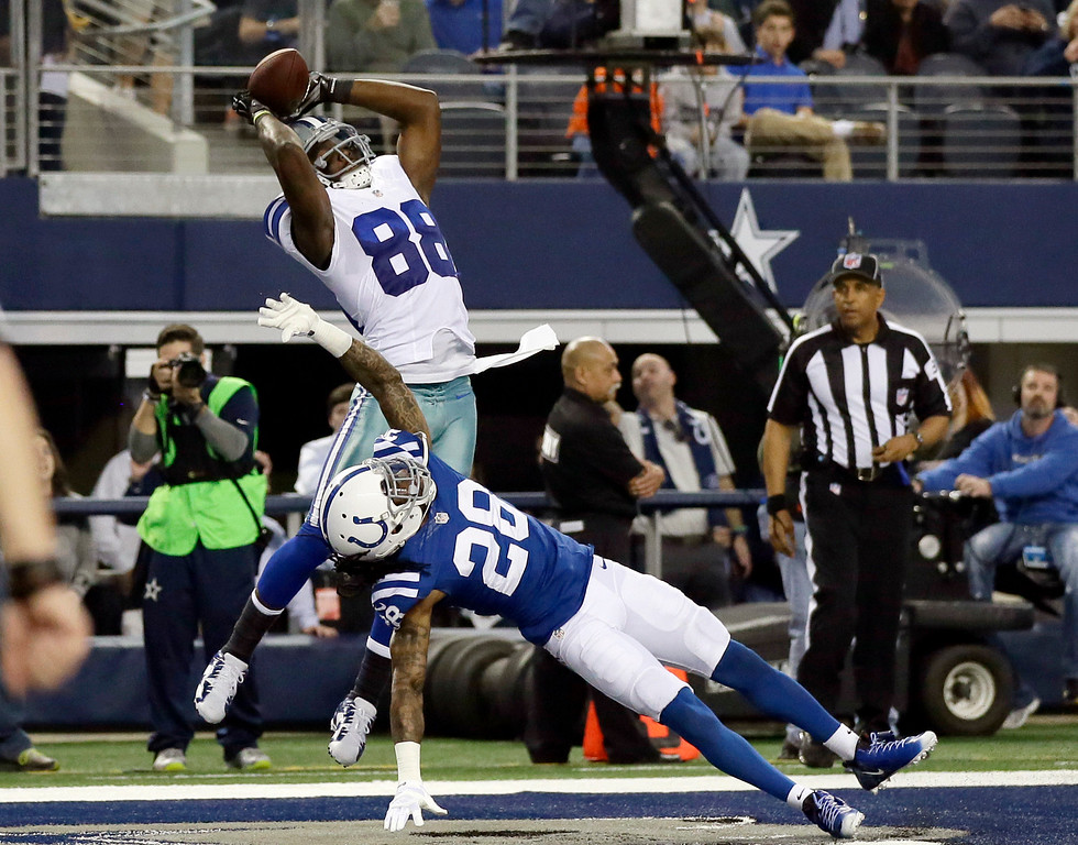 . Dallas Cowboys wide receiver Dez Bryant (88) reaches up to grab a touchdown pass over Indianapolis Colts cornerback Greg Toler (28) during the first half of an NFL football game, Sunday, Dec. 21, 2014, in Arlington, Texas. (AP Photo/Tim Sharp)