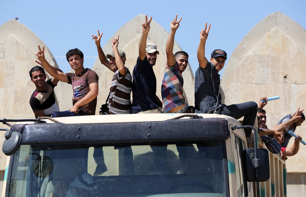 . Iraqi volunteers to fight along side the Iraqi security forces against Jihadist militants, flah the sign of victory as they leave a recruitment center aboard military trucks on June 15, 2014 in the Iraqi capital Baghdad. Faced with a militant offensive sweeping south toward Baghdad, Prime Minister Nuri al-Maliki announced the Iraqi government would arm and equip civilians who volunteer to fight, and thousands have signed up.  AFP PHOTO/AHMAD AL-RUBAYE