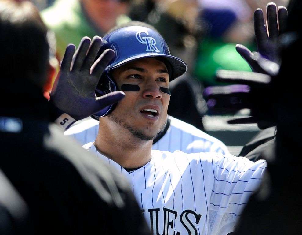 . Colorado Rockies\' Carlos Gonzalez is congratulated by teammates after scoring a run against the New York Mets during the sixth inning of a baseball game on Thursday, April 18, 2013, in Denver. (AP Photo/Jack Dempsey)