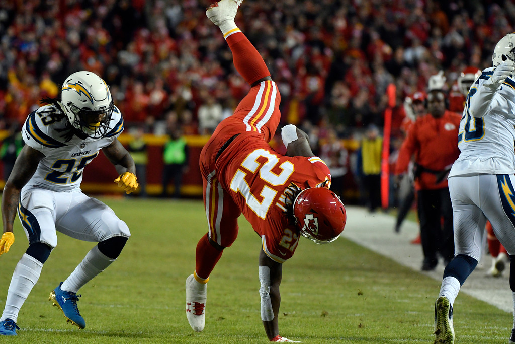 . Kansas City Chiefs running back Kareem Hunt (27) is upended after a tackle by Los Angeles Chargers defensive back Desmond King, right, as safety Rayshawn Jenkins (25) follows, during the first half of an NFL football game in Kansas City, Mo., Saturday, Dec. 16, 2017. (AP Photo/Ed Zurga)
