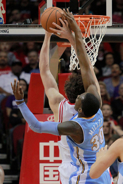 . Denver Nuggets forward Quincy Miller blocks the shot of Houston Rockets center Omer Asik during an NBA basketball game in Houston on Sunday, April 6, 2014. (AP Photo/Richard Carson)