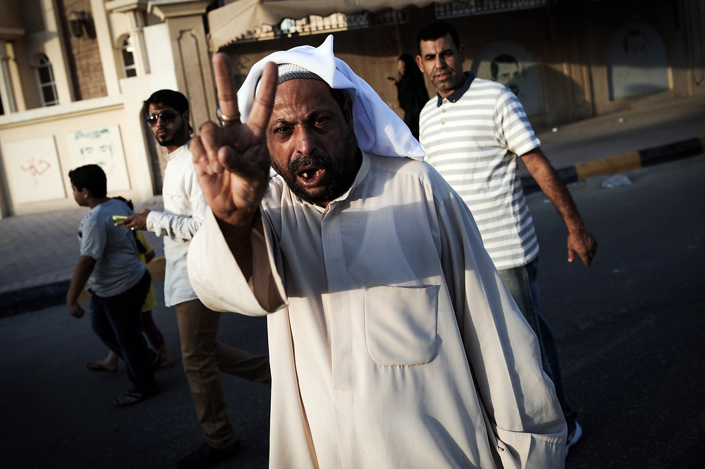 . A Bahraini man flashes the v-sign during the funeral of 10-year-old Ali Jaffer Habib, in the village of Malikiya, on August 10, 2013. Habib, according to his family, died after developing cancer due to the inhalation of tear gas fired by security forces earlier in the year. MOHAMMED AL-SHAIKH/AFP/Getty Images