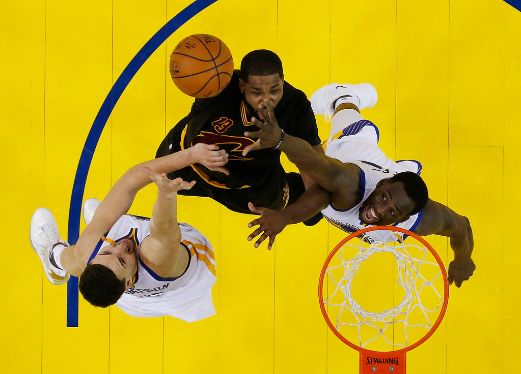 . Cleveland Cavaliers\' Tristan Thompson, center, is defended by Golden State Warriors\' Draymond Green, right, and Klay Thompson during the second half in Game 2 of basketball\'s NBA Finals Sunday, June 4, 2017, in Oakland, Calif. (AP Photo/Marcio Jose Sanchez, Pool)