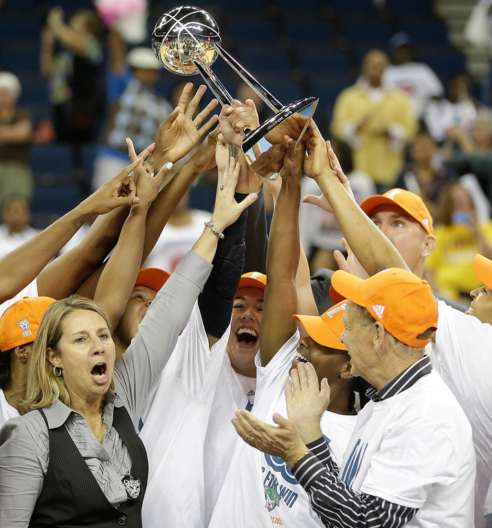 . Minnesota Lynx head coach Cheryl Reeve, left, and team hold the championship trophy after the second half of Game 3 of the WNBA Finals basketball series, in Duluth, Ga., Thursday, Oct. 10, 2013. The Minnesota Lynx won 86- 77. (AP Photo/John Bazemore)