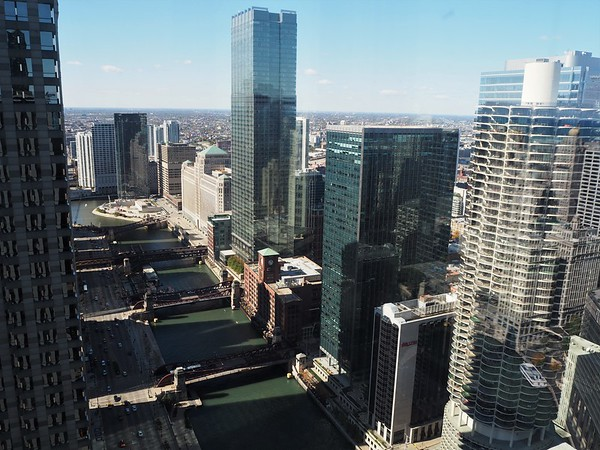 View from tall building of green river passing big city buildings, and crossed by bridges