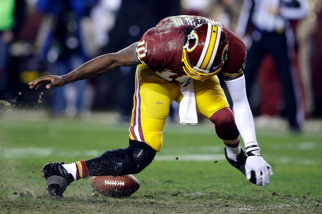 . Washington Redskins quarterback Robert Griffin III twists his knee as he reaches for the loose ball after a low snap during the second half of an NFL wild card playoff football game against the Seattle Seahawks in Landover, Md., Jan. 6, 2013. Griffin had his lateral collateral ligament repaired and his ACL reconstructed for a second time. The surgery was performed Wedensday Jan. 9, 2013 in Florida. (AP Photo/Matt Slocum, File)
