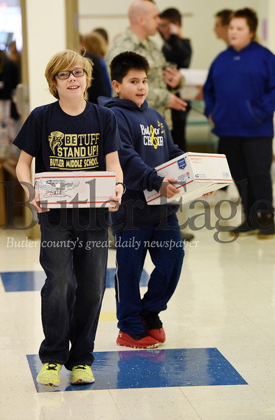Harold Aughton/Butler Eagle: Sixth Graders from Mrs. Hovanick's class, Logan Rogers and Brodie carry care packages to the truck for soldiers serving abroad, Friday, Nov. 22, 2019.