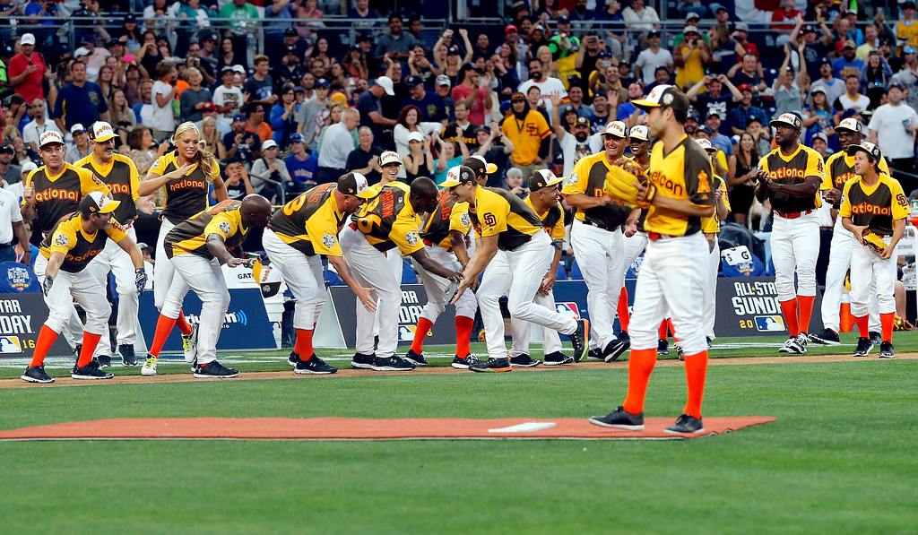 . New Orleans Saints quarterback Drew Brees greets teammates after hitting a home run during the All-Star Legends & Celebrity Softball game, Sunday, July 10, 2016, in San Diego. (AP Photo/Lenny Ignelzi)