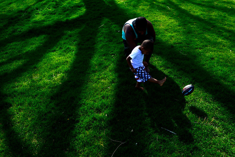 . Tre Virdure plays football with his son Tre Christian Vidure, 2, at Washington Park. Temperatures reached the low 80s in Denver. (Photo by AAron Ontiveroz/The Denver Post)