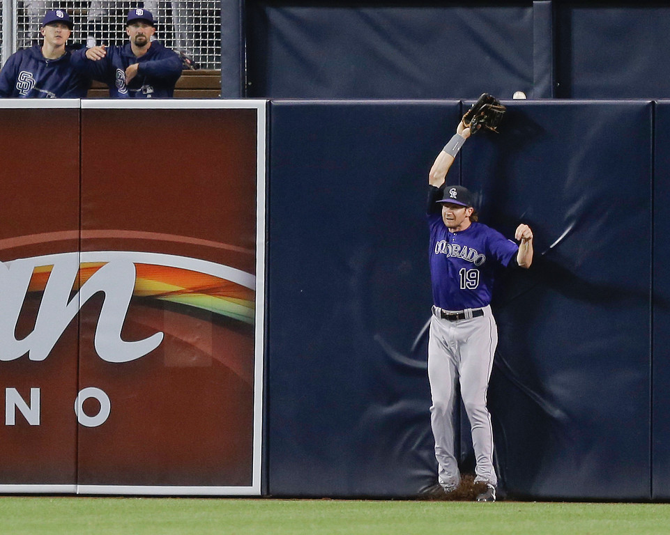 . Colorado Rockies center fielder Charlie Blackmon backs into the fence as the home run ball hit by San Diego Padres\' Carlos Quentin just crawls over in the sixth inning of a baseball game in San Diego, Wednesday, July 10, 2013. (AP Photo/Lenny Ignelzi)