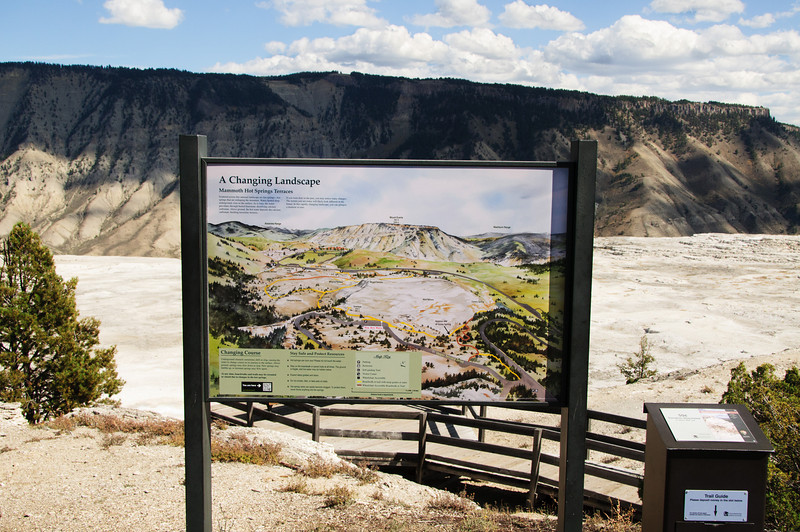 "29 Nov 13.  The image for today is one designed to give you an overview for several of the images to follow in the next couple of weeks. The vast majority of the image is a signboard hosting a map of the Mammoth Hot Springs. I've annotated  it with one missing aspect of the area, Grassy Spring, which was the topic of last Friday's (22 Nov) image. I suggest you keep this image around for a few weeks, or just print it out, as it may be helpful in understanding my descriptions of the area. This is the view looking straight ahead at the location marked on the signboard as ""you are here"" so it gives you the big picture. Zoom in and have a look around. The majority of the images I'll be sharing will be from locations in the lower right quadrant. Other than enhance the sky a wee bit, this is straight from the camera. Nikon D300s; 18 - 200; Aperture Priority; ISO 200; 1/800 sec @ f / 9."