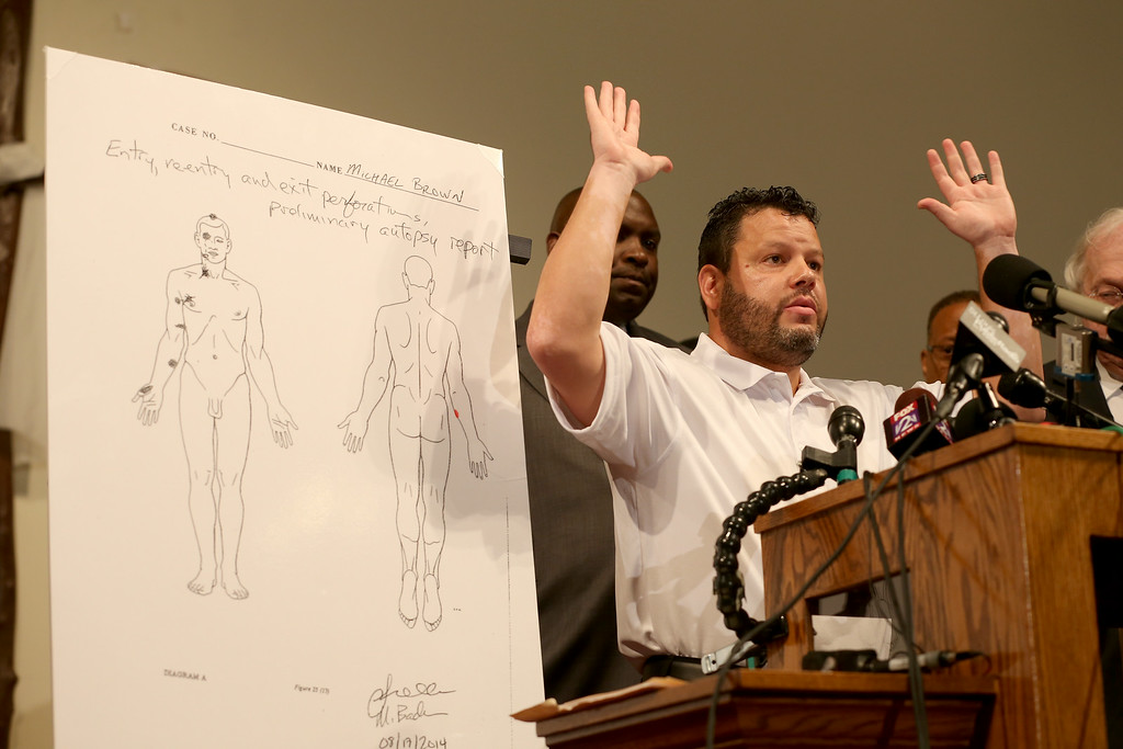 . Shawn Parcells, a forensic pathologist who assisted in the autopsy of Michael Brown stands near an autopsy diagram showing where the gun shots hit Michael Brown as he speaks about the findings during a press conference at  the Greater St. Marks Family Church on August 18, 2014 in Ferguson, Missouri. Unarmed teenager Michael Brown was shot and killed by a Ferguson police officer on August 9th.  (Photo by Joe Raedle/Getty Images)