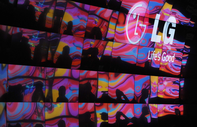 . Attendees and images from other 4K TVs are reflected in the curved 4K 3D Cinema display at LG\'s booth at the 2014 International Consumer Electronics Show (CES) on January 10, 2014 in Las Vegas. (Robyn Beck/AFP/Getty Images)